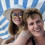 parent-and-teen-laughing-under-the-shade-2021-04-05-10-10-44-utc